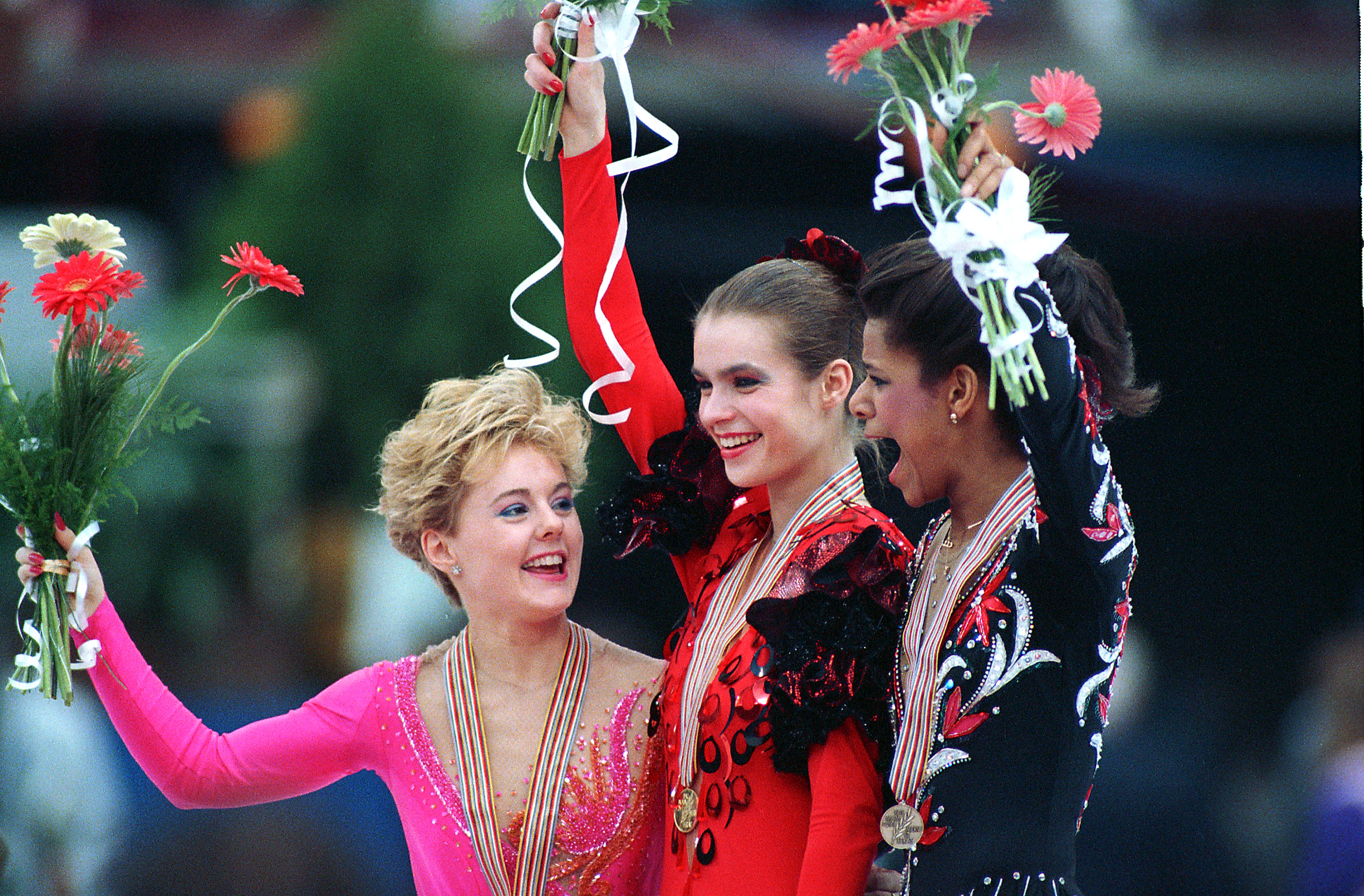 Katarina Witt of East Germany is flanked by Canadian Elizabeth Manley, left, and U.S. skater Debi Thomas during the medal ceremony following the World Figure Skating Championships in Budapest, Hungary, Saturday, March 26, 1988. AP Photo/Dave Caulkin.